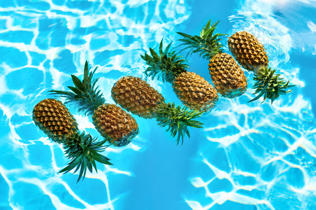 Photo pour Healthy Raw Organic Food. Fresh Ripe Pineapples Floating In Pure Water In Swimming Pool. Juicy Fruit. Vegetarian, Vegan Nutrition, Lifestyle. Eating Vitamins. Diet, Beauty, Health, Hydration Concept - image libre de droit