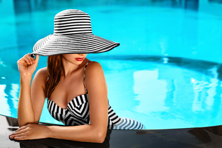 Photo for Summer Woman Body Care. Beautiful Sexy Girl With Healthy Skin In Elegant Striped Bikini, Sun Hat Relaxing In Swimming Pool Water In Resort Spa Hotel On Travel Holidays Vacation. Enjoyment. Lifestyle - Royalty Free Image