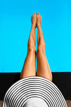 Foto de Summer Woman Body Care. Beautiful Sexy Long Fit Female Legs With Healthy Skin In Swimming Pool Water In Resort Spa Hotel On Travel Holidays Vacation. Beauty, Health, Wellness Concept. - Imagen libre de derechos