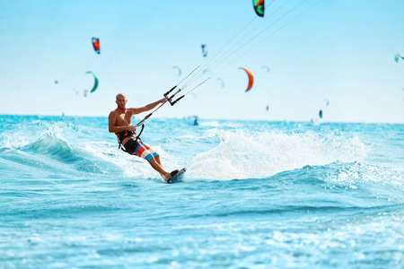 Photo pour Recreational Sports. Healthy Man Kiteboarding ( Kite Surfing ) On Waves In Sea Water. Extreme Sport Action. Summer Fun, Adventure, Holidays Travel Vacation. Active Lifestyle. Leisure Sporting Activity - image libre de droit