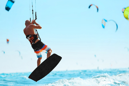 Water Sports. Kiteboarding, Kitesurfing. Kiter Jumping On Waves In Ocean. Extreme Sport Action. Recreational Sporting Activity. Healthy Active Lifestyle. Summer Fun, Adventure, Travel Vacation. Hobby