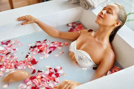 Foto de Spa Relaxation. Woman Body Care. Beautiful Sexy Caucasian Blonde Girl In Bikini Lying In Flower Bath In Resort Day Spa Salon. Beauty Treatment, Skin Care Therapy. Wellness. Healthy Lifestyle Concept - Imagen libre de derechos