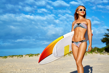 Foto de Water Sports. Surfing. Healthy Happy Sexy Fit Surfer Woman, Girl In Bikini Having Fun With Surfboard On Sea Beach. Summer Holidays Vacation. Lifestyle. Leisure Sporting Activity. Summertime Relaxation - Imagen libre de derechos