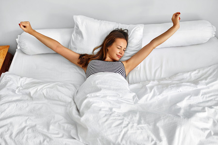 Photo pour Morning Wake Up. Smiling Young Woman Waking Up Fully Rested On White Bedding. Model Stretching In Bed. Girl Lying, Relaxing In Bedroom. Healthy Sleep, Lifestyle. Wellness, Health, Beauty Concept - image libre de droit