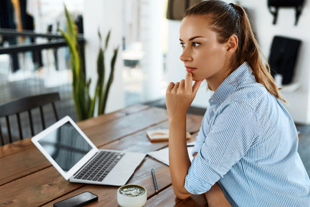 Photo for Learning, Studying. Portrait Of Beautiful Student Woman Using Laptop Computer, Notebook, Thinking At Cafe. Female Freelancer Working. Freelance Work, Business People Concept - Royalty Free Image