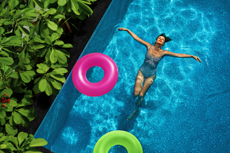 Photo for Summer Holidays. Sexy Happy Young Woman With Perfect Fit Body In Fashion Swimsuit Enjoying Vacation, Float Swim Rings  Floating In Swimming Pool Water At Tropical Resort. Healthy Lifestyle. Wellness - Royalty Free Image