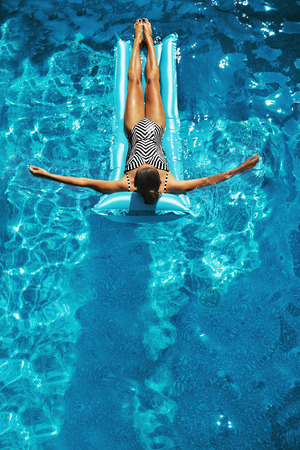 Foto de Summer Vacations. Beautiful Sexy Happy Smiling Woman With Fit Body, Healthy Skin In Swimwear Sunbathing, Floating On Float Swim Air Mattress, Rings In Swimming Pool Water. Beauty, Wellness. Recreation - Imagen libre de derechos
