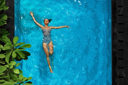 Photo for Woman In Pool Water. Beautiful Happy Girl With Sexy Fit Body Relaxing, Floating In Swimming Pool At Spa Hotel. Summer Holidays Vacation. Healthy Lifestyle. Wellness, Beauty, Health Concept. Recreation - Royalty Free Image