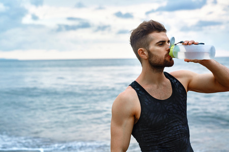Photo pour Man Drinking Water After Running Workout At Beach. Portrait Of Thirsty Healthy Athletic Male With Fit Body Drinking Refreshing Drink, Resting After Running Or Training Outdoor. Sports, Fitness Concept - image libre de droit