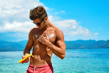 Photo pour Man Skin Care In Summer. Handsome Male With Sexy Body In Sunglasses Applying UV Protective Sunscreen Lotion Before Sunbathing, Tanning At Beach Using Solar Sun Block Protection Cream For Healthy Tan. - image libre de droit