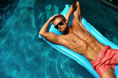 Photo for Summer Man Body Sun Skin Care. Beautiful Model With Sexy Body In Swimwear Tanning, Floating On Mattress In Swimming Pool Water. Fitness Male With Healthy Tan Relaxing At Relax Spa Resort. Summertime - Royalty Free Image