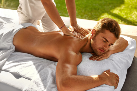 Photo pour Spa Body Massage. Close Up Beautiful Sexy Healthy Happy Man Enjoying Relaxing Back Massage In Outdoor Day Beauty Salon. Masseur Hand Massaging Male With Aromatherapy Oil. Skin Care Treatment Concept - image libre de droit