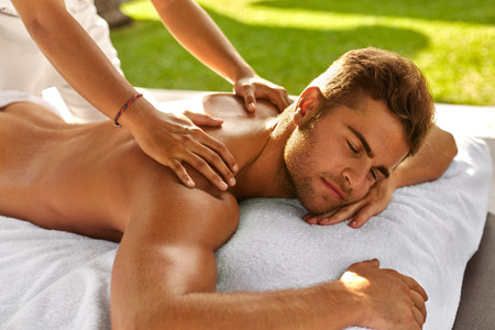Foto de Spa Massage For Man. Close Up Of Handsome Healthy Smiling Man Enjoying Relaxing Back Massage At Outdoor Beauty Salon. Masseuse Massaging Male Body With Aromatherapy Oil. Skin Care Treatment Concept - Imagen libre de derechos