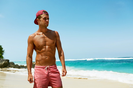 Photo pour Sexy Man On Beach In Summer. Handsome Male With Fit Body, Healthy Skin Sun Tan Tanning Near Sea At Luxury Relax Spa Resort. Beautiful Happy Guy Relaxing, Enjoying Holidays Travel Vacation. Summertime - image libre de droit