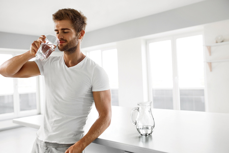 Foto de Closeup Portrait Of Handsome Young Man With Sexy Fit Body Drinking Fresh Water From Glass In Morning. - Imagen libre de derechos