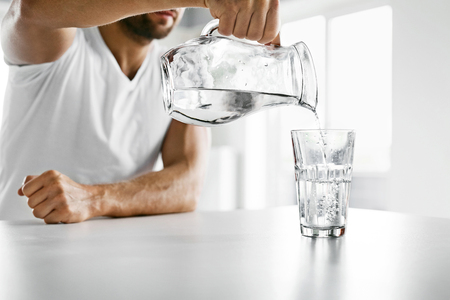 Photo for Drink Water. Close Up Of Handsome Young Man Pouring Fresh Pure Water From Pitcher Into A Glass In Morning In Kitchen. Beautiful Athletic Male Model Feeling Thirsty. Healthy Nutrition And Hydration - Royalty Free Image