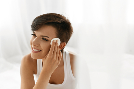 Photo for Beauty Skin Care. Beautiful Happy Woman Removing Face Makeup Using Cotton Pad. Closeup Portrait Of Healthy Smiling Female Model With Natural Makeup Touching Perfect Fresh Soft Skin, Cleaning Her Face - Royalty Free Image
