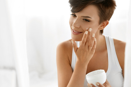 Photo pour Beauty Skin Care. Beautiful Happy Woman Applying Cosmetic Cream On Clean Face. Closeup Portrait Of Healthy Smiling Female Model With Natural Makeup, Fresh Soft Pure Skin Applying Moisturizing Lotion - image libre de droit