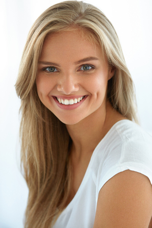 Photo pour Beauty Woman Portrait. Closeup Of Beautiful Happy Girl With Perfect Smile, White Teeth Smiling At Camera. Attractive Healthy Young Female With Fresh Natural Face Makeup Indoors. High Resolution Image - image libre de droit