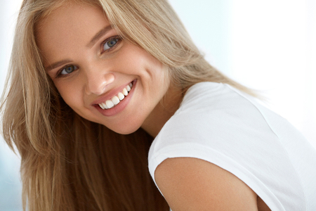 Foto de Beauty Woman Portrait. Closeup Of Beautiful Happy Girl With Perfect Smile, White Teeth Smiling At Camera. Attractive Healthy Young Female With Fresh Natural Face Makeup Indoors. High Resolution Image - Imagen libre de derechos