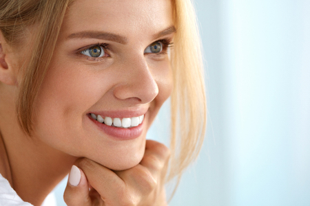 Photo pour Beauty Woman Portrait. Beautiful Happy Smiling Girl With Perfect White Smile, Blonde Hair And Fresh Face Touching Her Healthy Soft Skin. Woman's Health, Skin Care Concept. High Resolution Image - image libre de droit