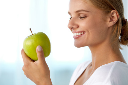 Photo pour Healthy Nutrition. Closeup Portrait Of Beautiful Smiling Woman With Perfect Smile, White Teeth And Fresh Face Eating Organic Green Apple. Dental Health, Diet Food Concepts. High Resolution Image - image libre de droit
