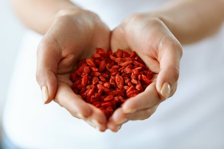 Photo for Organic Diet Food. Closeup Of Young Woman Hands With Natural Nails Holding Tasty Ripe Sweet Red Sun Dried Goji Berries, Natural Vitamin Snack. Healthy Nutrition, Raw Eating Concept. High Resolution - Royalty Free Image