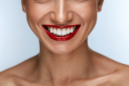 Photo pour Beautiful Smile With Healthy White Teeth And Red Lips. Closeup Of Smiling Woman Mouth With Plump Full Lips With Perfect Red Lipstick Makeup. Teeth Whitening, Dental Health Concepts. High Resolution - image libre de droit