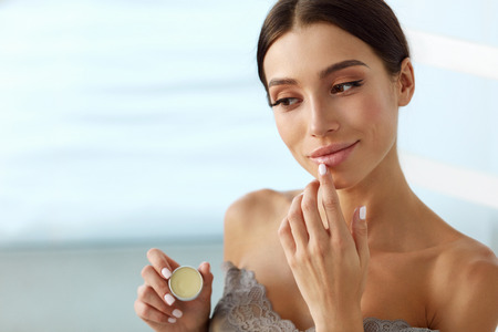 Photo pour Lips Skin Care. Beautiful Woman With Beauty Face Applying Lip Balsam, Lipbalm On Full Sexy Lips. Portrait Of Smiling Female Model With Soft Skin And Natural Nude Makeup Touching Lips. High Resolution - image libre de droit