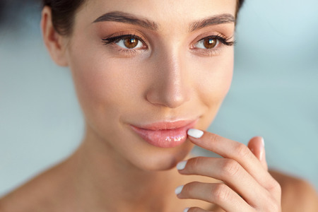 Photo pour Beauty Face. Beautiful Woman With Natural Makeup And Sexy Full Lips Touching Her Mouth. Closeup Portrait Of Smiling Model Girl With Healthy Smooth Facial Skin Applying Lip Balm On Lip. High Resolution - image libre de droit