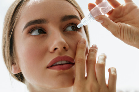 Foto de Vision And Ophthalmology Medicine. Closeup Of Beautiful Woman Applying Eyedrops In Her Eyes. Young Female Model With Natural Makeup Using A Bottle Of Eye Drops. Health Concept. High Resolution - Imagen libre de derechos