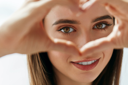 Photo pour Healthy Eyes And Vision. Portrait Of Beautiful Happy Woman Holding Heart Shaped Hands Near Eyes. Closeup Of Smiling Girl With Healthy Skin Showing Love Sign. Eyecare. High Resolution Image - image libre de droit