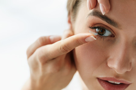 Foto de Contact Lens For Vision. Closeup Of Female Face With Applying Contact Lens On Her Brown Eyes. Beautiful Woman Putting Eye Lenses With Hands. Opthalmology Medicine And Health. High Resolution  - Imagen libre de derechos