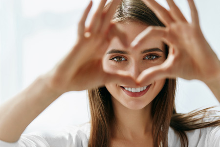 Foto per Healthy Eyes And Vision. Portrait Of Beautiful Happy Woman Holding Heart Shaped Hands Near Eyes. Closeup Of Smiling Girl With Healthy Skin Showing Love Sign. Eyecare. High Resolution Image - Immagine Royalty Free