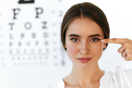 Photo pour Health And Visual Concept. Closeup Of Beautiful Smiling Woman With Healthy Eyes In Front Of Visual Eye Test Board. Portrait Of Happy Girl Pointing At Her Eyes With Finger. High Resolution Image - image libre de droit