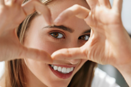 Foto de Healthy Eyes And Vision. Portrait Of Beautiful Happy Woman Holding Heart Shaped Hands Near Eyes. Closeup Of Smiling Girl With Healthy Skin Showing Love Sign. Eyecare. High Resolution Image - Imagen libre de derechos