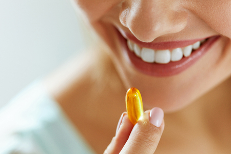 Photo pour Vitamin And Supplement. Closeup Of Beautiful Young Woman Taking Yellow Fish Oil Pill. Female Hand Putting Omega-3 Capsule In Mouth. Healthy Eating And Diet Nutrition Concepts. High Resolution Image - image libre de droit