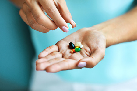 Photo pour Vitamins And Supplements. Closeup Of Female Hand Holding Variety Of Colorful Pills On Palm. Close-up Of Woman Fingers Taking Medication Tablets, Capsules From Hand. Medicine Concept. High Resolution - image libre de droit