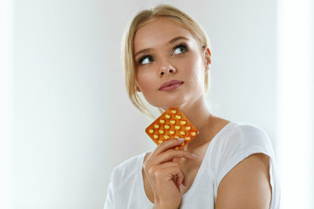 Photo pour Woman With Birth Control Pills. Healthy Beautiful Girl Holding Blister Pack With Oral Contraceptive Pills In Hand And Thinking Should She Take A Pill. Medicine, Health Care Concept. High Resolution - image libre de droit