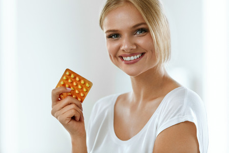 Photo pour Woman With Birth Control Pills. Beautiful Smiling Girl Holding Blister Pack With Oral Contraceptive Pills. Healthy Happy Girl With Pill Package In Hand. Medicine, Health Care Concept. High Resolution - image libre de droit