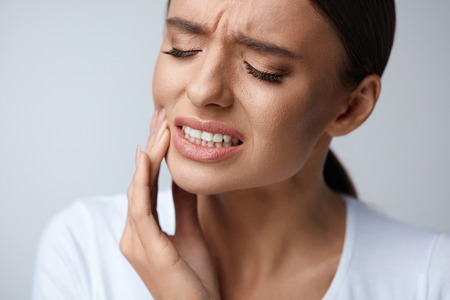Foto de Tooth Pain And Dentistry. Beautiful Young Woman Suffering From Terrible Strong Teeth Pain, Touching Cheek With Hand. Female Feeling Painful Toothache. Dental Care And Health Concept. High Resolution - Imagen libre de derechos
