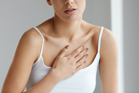 Photo pour Heart Health Care. Closeup Of Young Woman Feeling Strong Pain In Chest. Close-up Of Female Body With Hand On Chest. Girl Suffering From Painful Feeling, Having Health Issues. High Resolution Image - image libre de droit