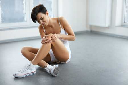 Photo pour Leg Pain. Beautiful Woman Feeling Pain In Knee. Attractive Female Suffering From Painful Knee, Joint Pain, Sitting On Floor And Touching, Massaging Her Leg. Health Issues Concept. High Resolution - image libre de droit