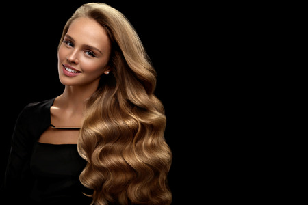 Photo pour Curly Blonde Hair. Beauty Model Girl With Perfect Makeup, Gorgeous Volume And Hair Color Standing On Black Background. Beautiful Smiling Woman With Healthy Long Shiny Wavy Hair Portrait. High Quality - image libre de droit