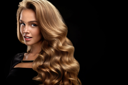 Photo for Beautiful Curly Hair. Female Beauty Model With Perfect Makeup, Gorgeous Volume And Blonde Hair Color. Attractive Smiling Woman With Healthy Long Shiny Wavy Hair On Black Background. High Resolution - Royalty Free Image