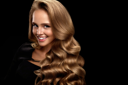 Photo for Hairstyle. Beautiful Woman With Healthy Long Shiny Blonde Wavy Curly Hair On Black Background. Portrait Of Smiling Girl Model With Nice Face Makeup Perfect Curls. Hair Beauty Concept. High Resolution - Royalty Free Image