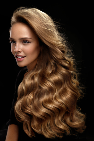 Photo pour Beautiful Long Hair. Fashion Female Model With Beauty Face Makeup And Healthy Shiny Blonde Wavy Curly Hair On Black Background. Portrait Of Woman With Gorgeous Hairstyle And Hair Color. High Quality - image libre de droit