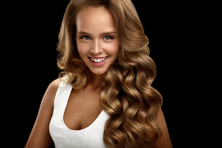 Photo pour Hairstyle. Beautiful Woman With Healthy Long Shiny Blonde Wavy Curly Hair On Black Background. Portrait Of Smiling Girl Model With Nice Face Makeup Perfect Curls. Hair Beauty Concept. High Resolution - image libre de droit