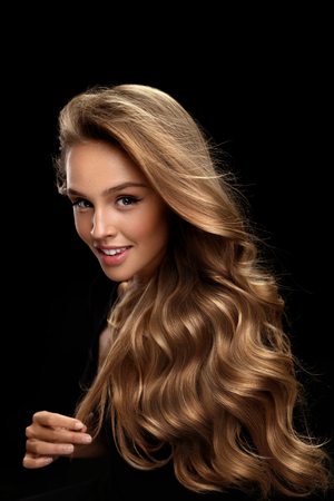 Photo for Curly Blonde Hair. Beauty Model Girl With Perfect Makeup, Gorgeous Volume And Hair Color Standing On Black Background. Beautiful Smiling Woman With Healthy Long Shiny Wavy Hair Portrait. High Quality - Royalty Free Image