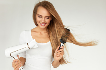 Photo pour Hair Care. Woman Drying Beautiful Long Straight Hair Using Dryer. Portrait Of Attractive Girl Model With Blonde Hair Using Hairdryer,  Round Brush For Hairdressing. Hairstyle Concept. High Resolution - image libre de droit